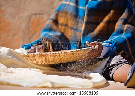 Portrait of African woman with a basket sieve straining sorghum, staple food in Africa - stock photo