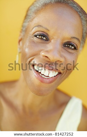 portrait of african 50 years old surprised woman with white hair, smiling on yellow background - stock photo
