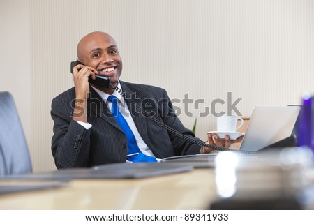 Portrait of Afro American businessman talking on telephone while holding cup of tea