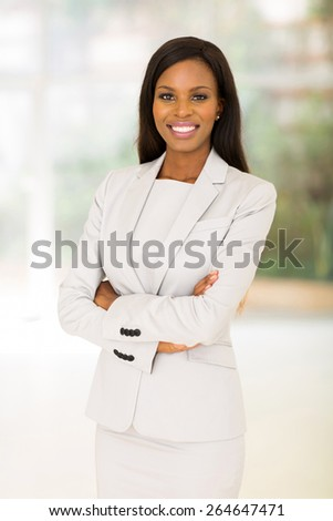 portrait of afro american businesswoman with arms crossed in office - stock photo