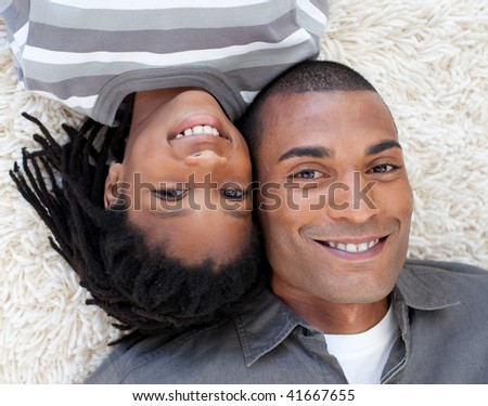 Portrait of Afro-American Father and his son on floor with heads together - stock photo