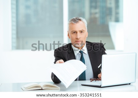 Portrait of aged businessman wearing suit and tie. Businessman in years is in office with big window. Boss using laptop and looking at camera
