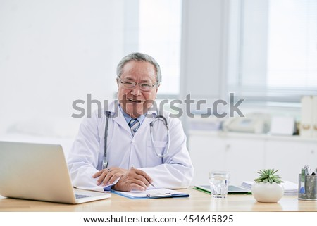 Portrait of aged Vietnamese doctor in his office