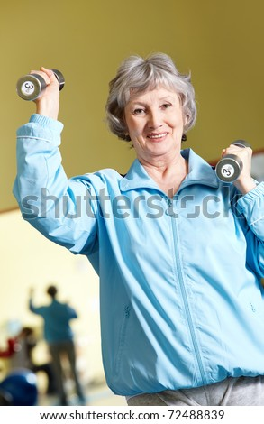 Portrait of aged woman doing physical exercise with barbells - stock photo