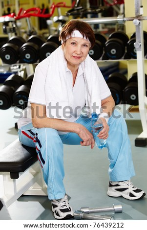 Portrait of aged woman with bottle of water in sport club - stock photo