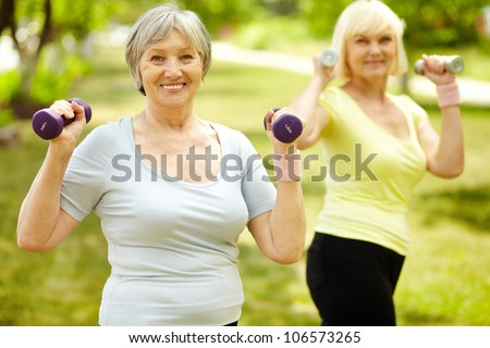 Portrait of aged women doing physical exercise with barbells - stock photo