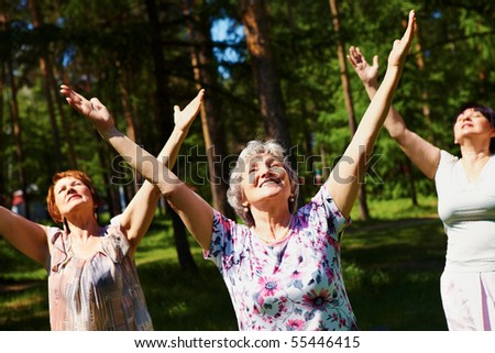 Portrait of aged women with their arms raised in praise - stock photo