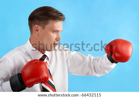 Portrait of aggressive businessman in boxing gloves fighting over blue background