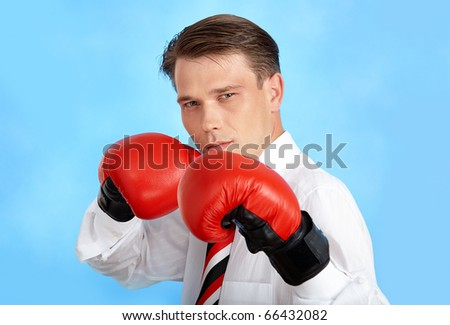 Portrait of aggressive businessman wearing boxing gloves over blue background