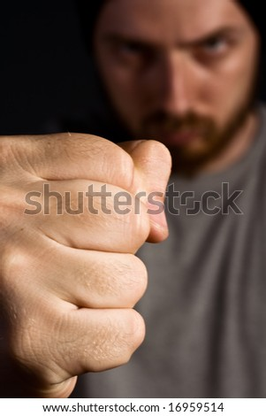Portrait of aggressive man showing his powerful fist