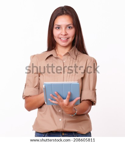 Portrait of alone friendly girl on brown blouse using her tablet pc while standing and smiling at you on isolated studio