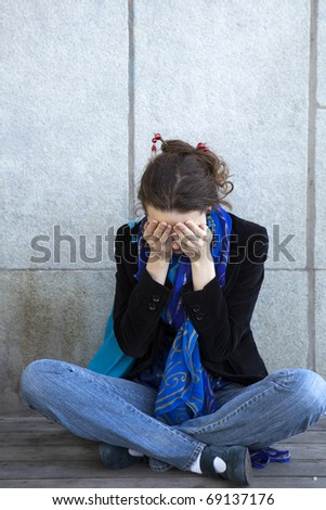 Portrait of alone young urban girl sitting at dirty wall look like  grunge background - stock photo