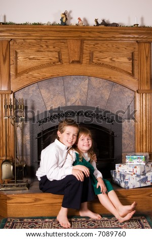 Portrait of am elementary brother and sister on the family hearth by a pile of wrapped Christmas gifts.