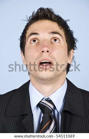 Portrait of amazed businessman with cool hairstyle looking up with mouth open and making big eyes - stock photo