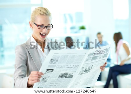 Portrait of amazed female looking surprisingly at newspaper in working environment