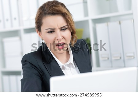 Portrait of amazed young business woman looking intently at laptop monitor - stock photo