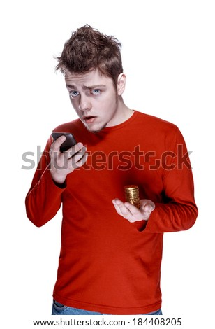 Portrait of amazed young guy with smartphone in one hand & golden coins in other - stock photo