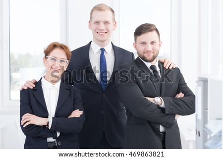 Portrait of ambitious smiling business people at office