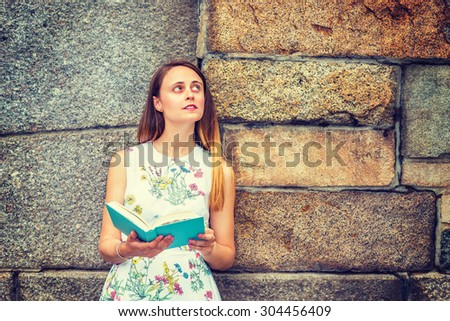 Portrait of American college student. A pretty girl wearing flower patterned, sleeveless, white dress, holding green book, standing against rocky wall, looking up, reading, thinking. Instagram effect  - stock photo