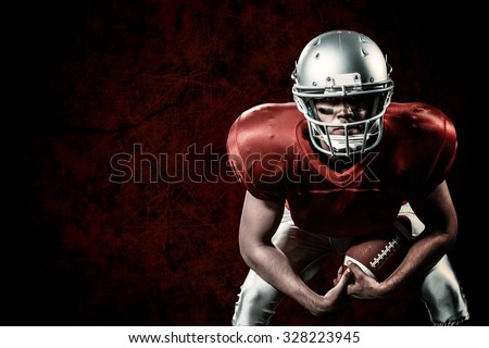Portrait of American football player bending while holding ball against dark background - stock photo
