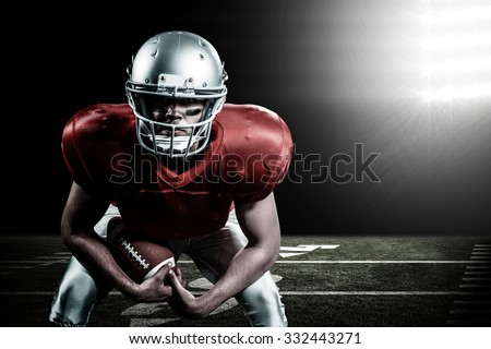 Portrait of American football player bending while holding ball against spotlight - stock photo