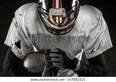 Portrait of american football player holding a ball and looking down - stock photo