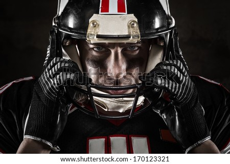 Portrait of american football player looking at camera with intense gaze - stock photo