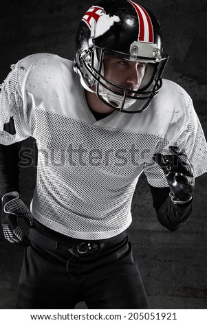 Portrait of american football player running on dark background - stock photo