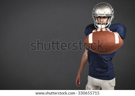 Portrait of American football player showing ball against grey