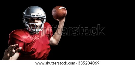 Portrait of American football player throwing ball against black