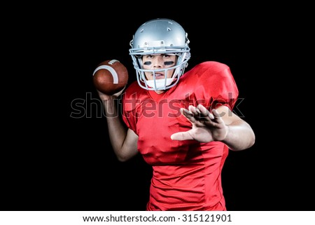 Portrait of American football player throwing ball against black background - stock photo