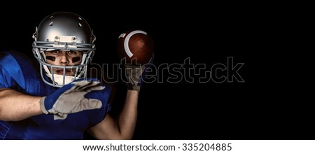 Portrait of American football player with ball playing against black