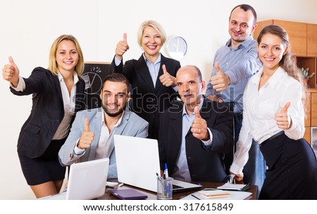 Portrait of american friendly relaxed employees sitting at desk