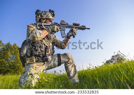 Portrait of American Soldier aiming his rifle on blue sky background - stock photo