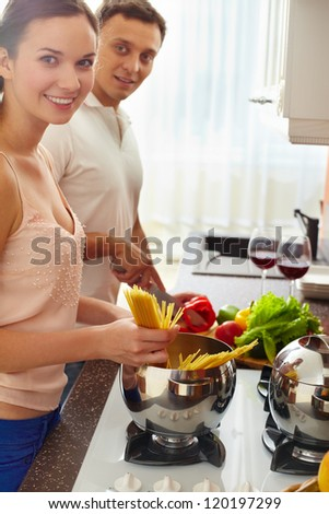 Portrait of amorous couple cooking spaghetti and salad in the kitchen