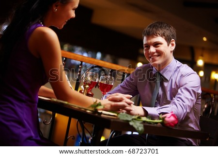 Portrait of amorous couple holding by hands in the cafe - stock photo