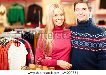 Portrait of amorous couple of shoppers looking at camera with smiles - stock photo