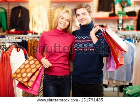 Portrait of amorous couple with paperbags looking at camera with smiles - stock photo