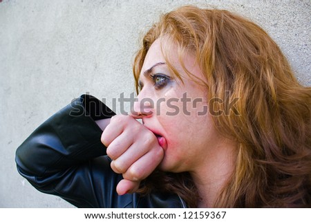 Portrait of an abused blond woman near a wall - stock photo