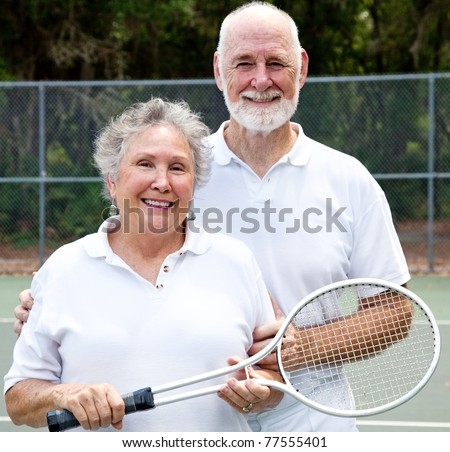 Portrait of an active senior couple on the tennis courts. - stock photo