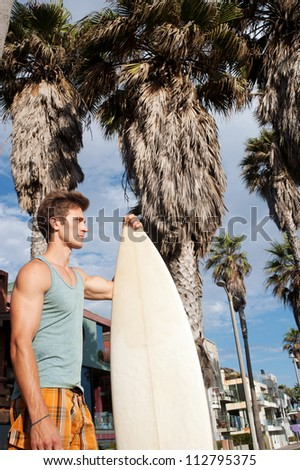 portrait of an active young man with a surfboard - stock photo