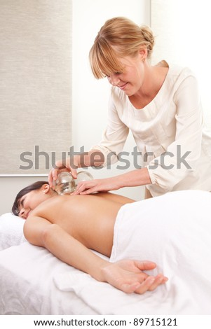 Portrait of an acupuncturist removing a glass globe in a fire cupping therapy session - stock photo