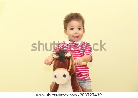 Portrait of an adorable african boy in his horse toy. - stock photo