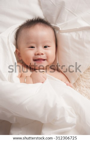 Portrait of an adorable baby boy crawling covered with white blanket