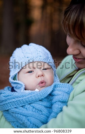 Portrait of an adorable baby boy in his mother's arms - stock photo