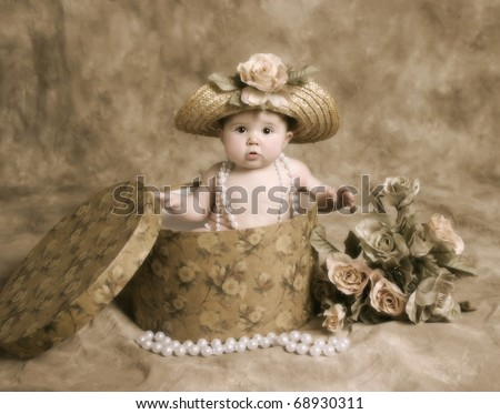 Portrait of an adorable baby girl playing dress up, sitting in a hatbox wearing a straw hat and pearl necklace