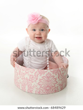 Portrait of an adorable baby girl sitting in a pink and white hatbox wearing a white shirt, pearl necklace, and pink headband with rose - stock photo