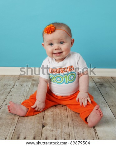 Portrait of an adorable baby girl sitting in front of a turquoise blue wall wearing a shirt that says Born in year - stock photo