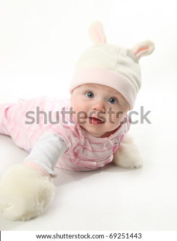 Portrait of an adorable baby girl wearing a bunny rabbit costume and furry mittens - stock photo