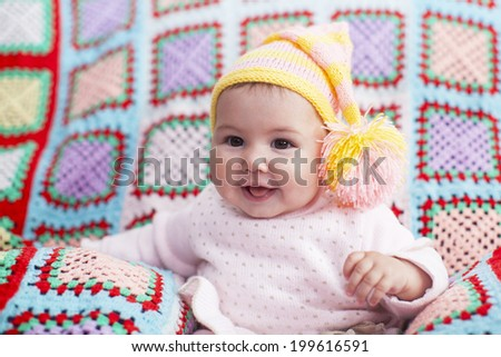 Portrait of an adorable baby girl wearing a knit pink and yellow winter hat - stock photo
